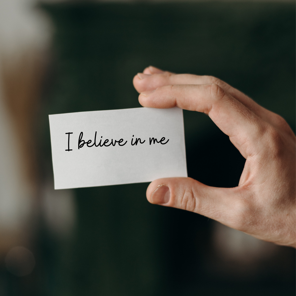 "a hand holding a card saying ""I believe in me"""