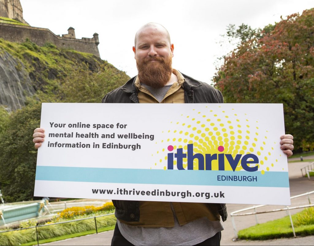 a man with a ginger beard in front of Edinburgh Castle holding a foam board saying 'Your online pace for mental health and wellbeing information in Edinburgh. iThrive Edinburgh. www.ithriveedinburgh.org.uk