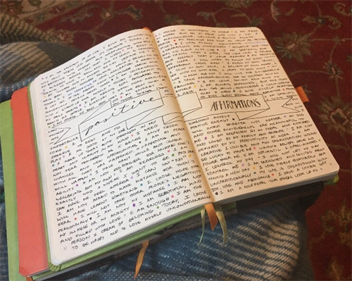 "An open journal full of notes with the words ""positive affirmations"""