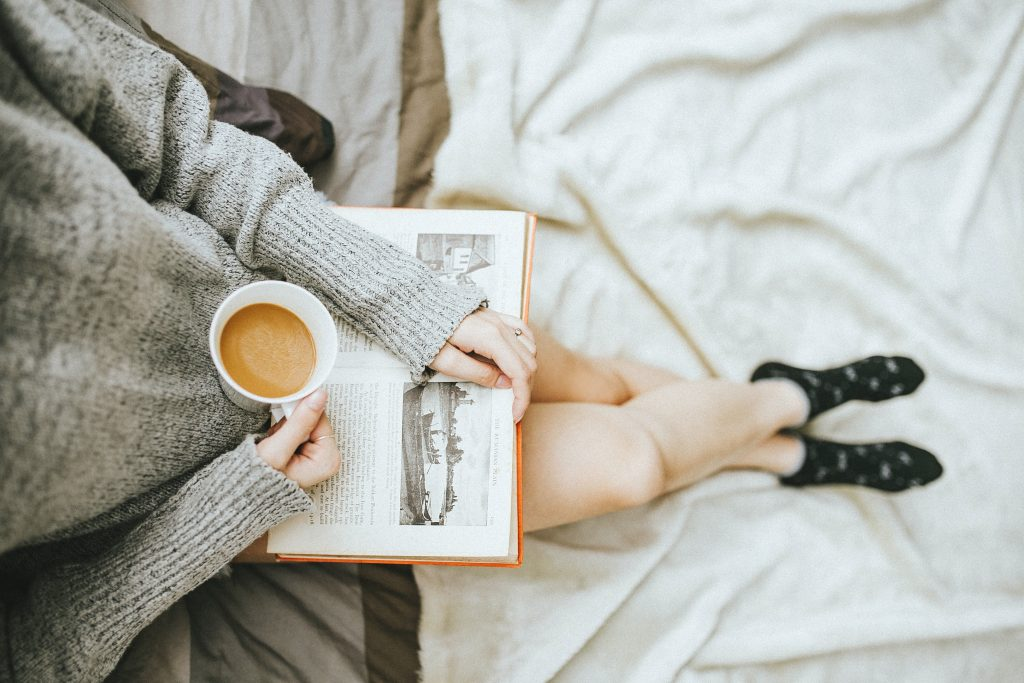 Person lying in bed reading a book and drinking a cup of tea. The figures head is out of shot.