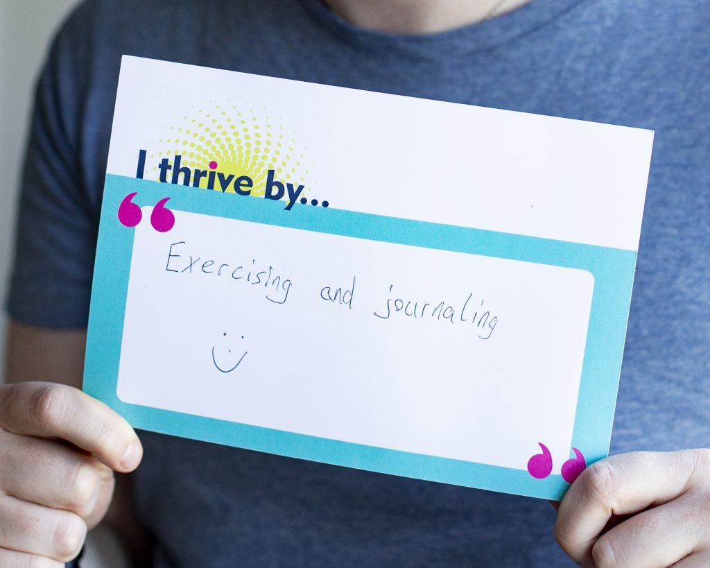 """Someone holding a postcard that says """"I thrive by... Exercising and journaling"""""""