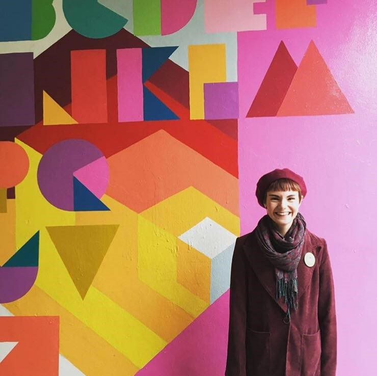 A women wearing a maroon beret, scarf and jacket with a button on it. They are smiling and looking at the camera. The back ground is multicoloured geometric patterns painted on the wall
